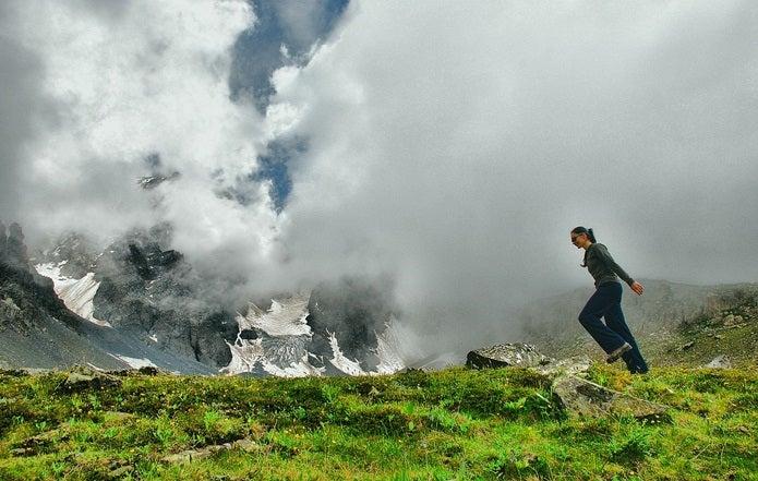 登山にサングラスを着用し歩く女性
