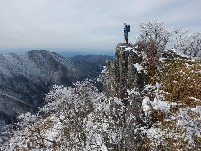 雪山の崖に立つ人