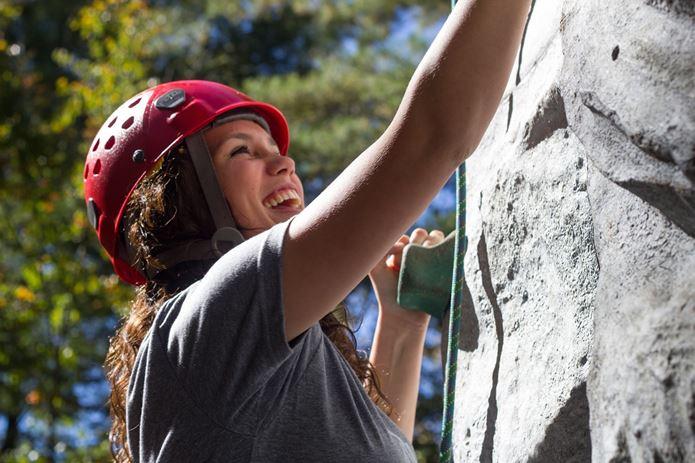 山の日にロッククライミングを楽しむ女性