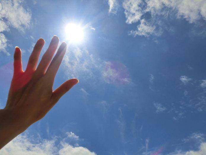 日中の日差しを手で遮る