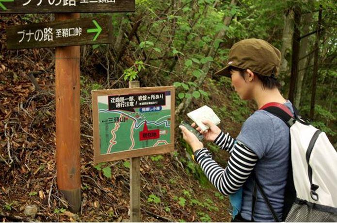 登山アプリと地図を見ている女性