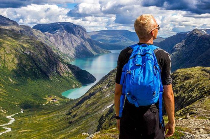 登山アプリをスマホにいれてザックを背負う男性