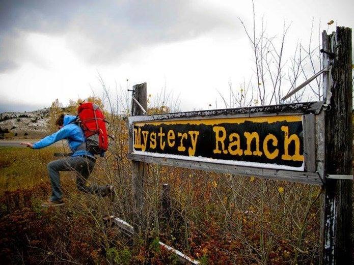 ミステリーランチのロゴとリュックを背負ってジャンプする男性
