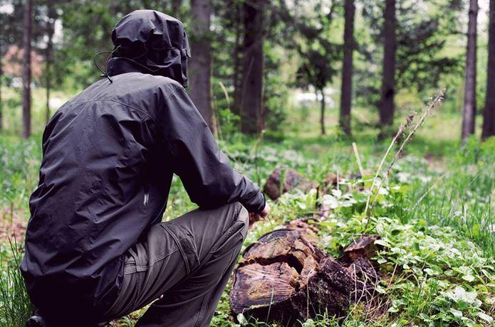 アークテリクスのマウンテンパーカーを着て森でしゃがむ人