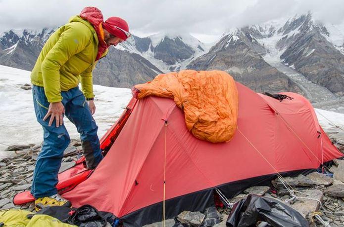 マウンテンイクイップメントのダウンジャケットを着ている男性とテント