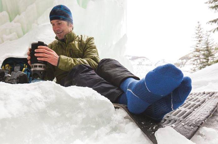 スマートウールの靴下を履いて雪の中にいる男性