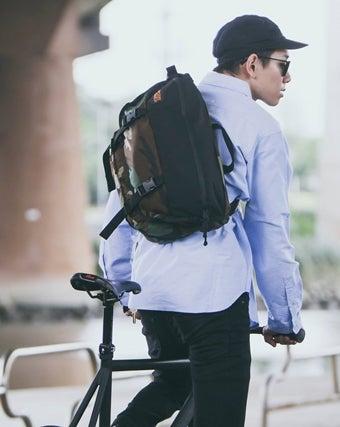 インベーダーを背負って自転車に乗る男性