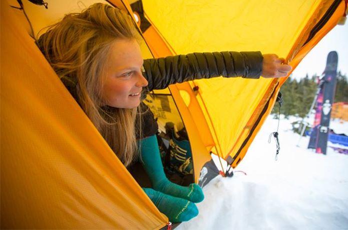 スマートウールの靴下を履いてテントから外を見る女性