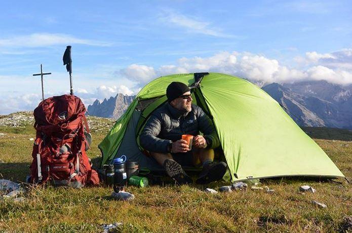 オスプレーのザックとテントと座る男性