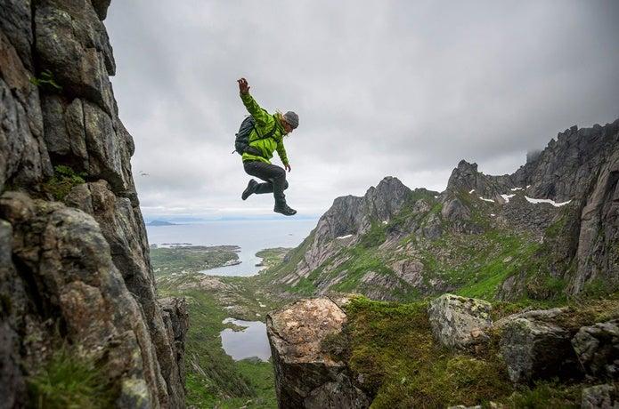 ノースフェイスのゴアテックスを着てジャンプする男性