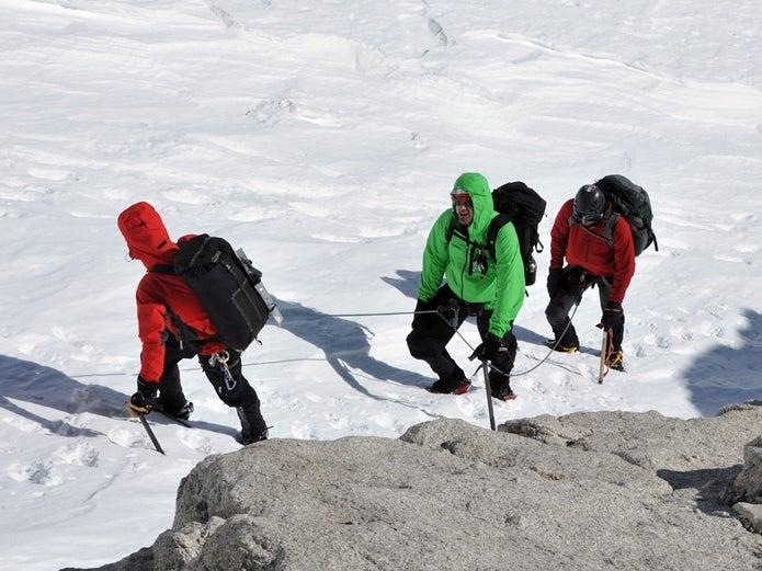 ザイルでお互いを繋いで雪山を登る登山者