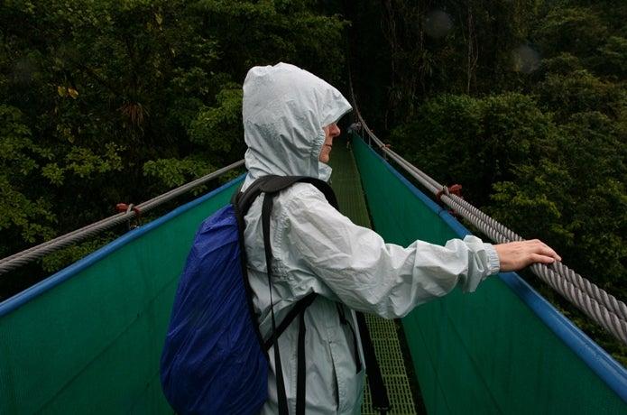 雨の中、橋を渡る女性