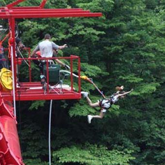 赤い橋からバンジージャンプする人