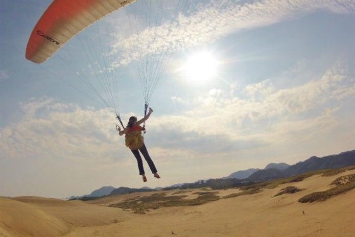 鳥取砂丘パラグライダー体験スクールで飛ぶ人