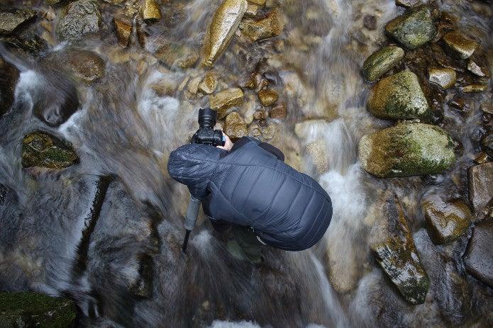 川の上で防水カメラを使う男性