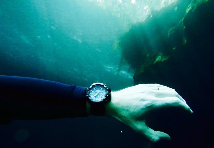 アウトドアの時計をつけて海にもぐる人の手