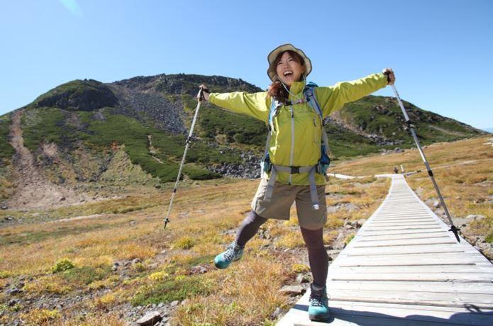 登山ファッションを着こなし山を歩く女性