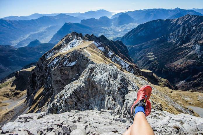サロモンのシューズを履いて山に座る人の足