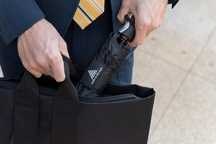 折り畳み傘をバッグにしまう人の手
