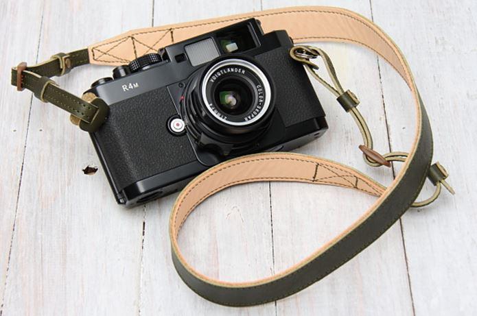 革のカメラストラップをつけたカメラ