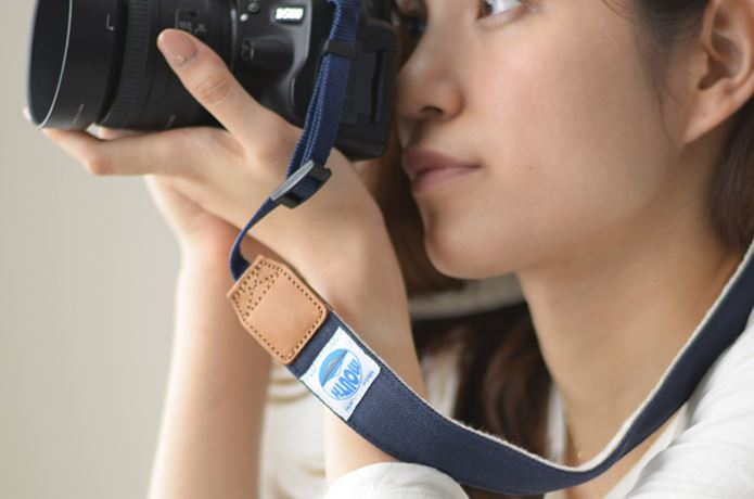 カメラストラップをつけて写真をとる女性