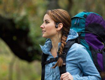 骨伝導イヤホンをつけて山を登る女性