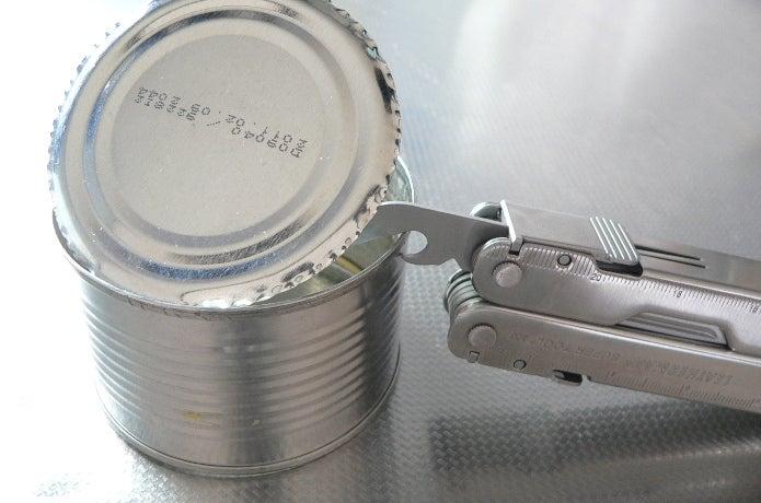缶切りで缶詰を開ける