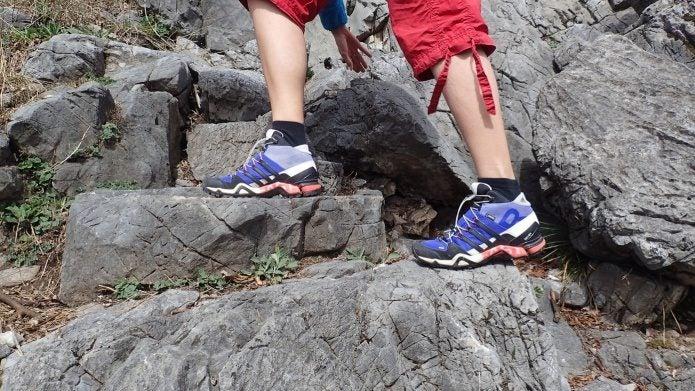アディダスのトレッキングシューズを履いて岩を登る足