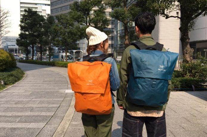 防水バックパックを背負う男女
