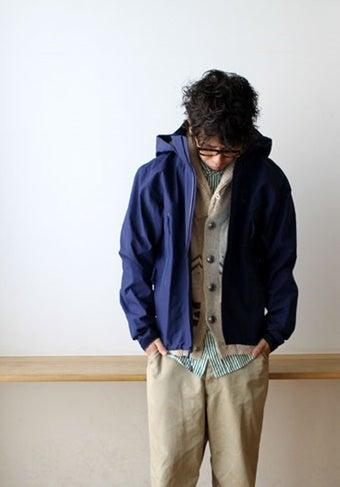 青いアウトドアウェアを着る男性