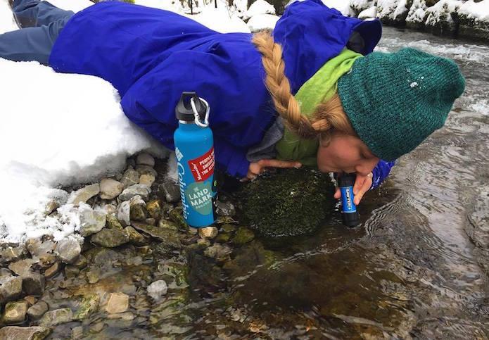 サバイバルグッズを使って川の水を飲む女性