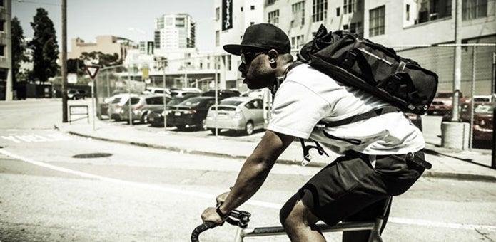 防水バッグを背負って自転車に乗る男性