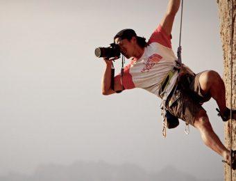 岩壁でカメラを構えるジミー・チン