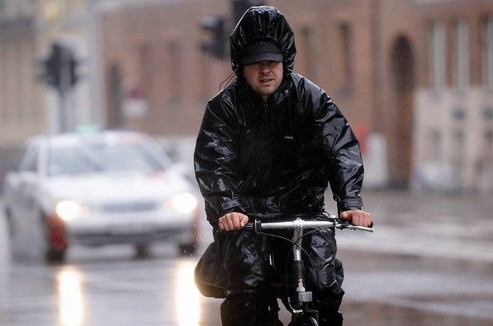 レインジャケットを着て自転車に乗る男性
