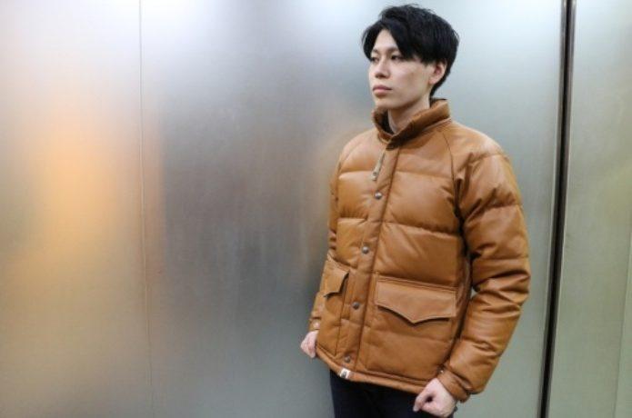 キャメルカラーのダウンジャケットを着た男性