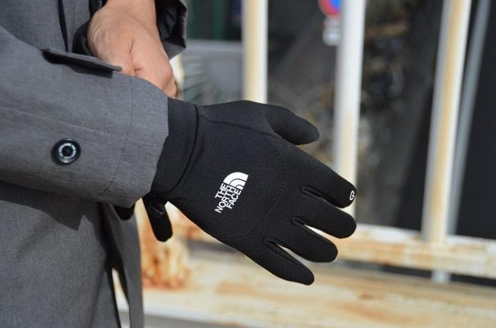 ノースフェイスの手袋をする男性