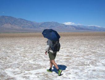 日よけに折り畳み傘を使う男性