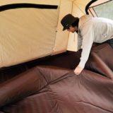 テントにインナーマットをひく男性