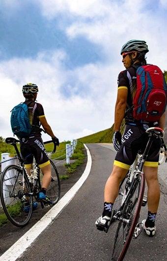 ドイターのロード用バックパックを背負って自転車をこぐ2人