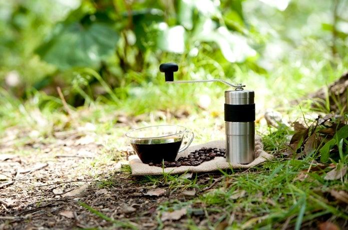 地面に置かれた手動コーヒーミルと1杯のコーヒー