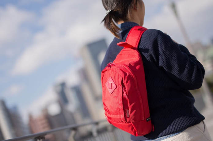コールマンの赤いバッグを背負った女性