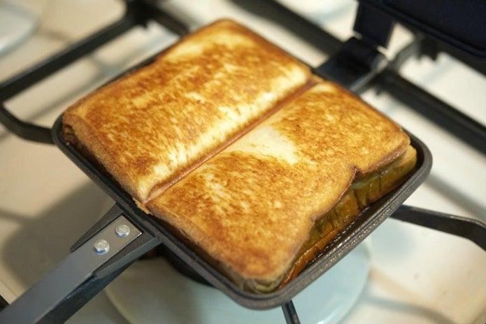 直火のホットサンドメーカーでパンをはさむ