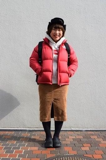 ノースフェイスのレッドカラーダウンを着た女性