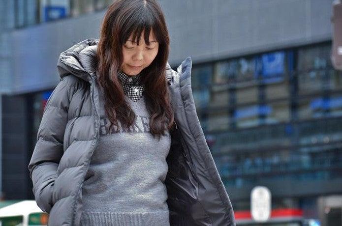 ノースフェイスのグレーカラーダウンを着た女性