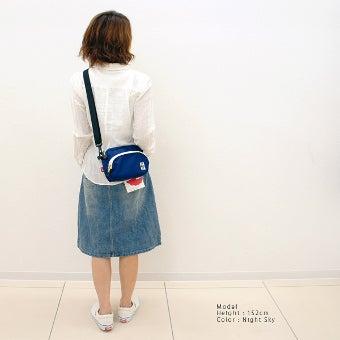 チャムスの青いショルダーバッグを持った女性