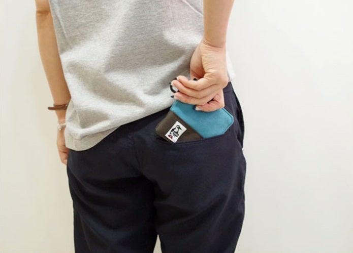 チャムスのコインケースをポケットから取り出す男性