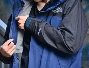 ノースフェイスのマウンテンジャケットを着てジップをあげる人