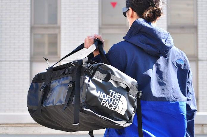 黒のノースフェイスのボストンバッグを持った男性