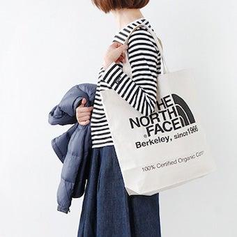ノースフェイスのトートバッグを使う女性