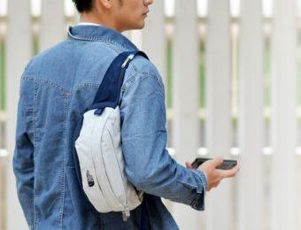 ノースフェイスのウエストバッグを肩にかけている男性